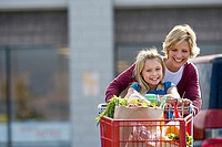 Mother and daughter 7-9 pushing shopping trolley in supermarket car park, smiling, front view, portrait