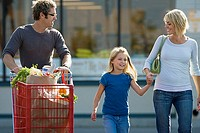 Family leaving supermarket, father pushing shopping trolley, mother and daughter 7-9 holding hands