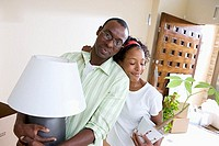 Couple moving house, woman with pot plant embracing husband, man carrying lamp, portrait tilt
