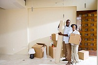 Couple moving house, standing in bare living room, woman holding box, man with rolled up carpet, portrait