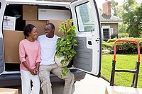 Couple moving house, sitting in rear of van, man holding pot plant, smiling