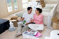 Couple moving house, sitting on floor in room, man unpacking glassware, woman looking at photographs