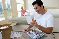 Couple moving house, woman unpacking, focus on man looking at photograph album in room, smiling tilt