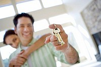 Couple standing in room, man holding aloft keys to new house, smiling, portrait tilt, differential focus