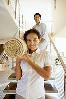Couple moving house, carrying rolled-up carpet on shoulders down staircase, front view, smiling, portrait