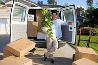 Man moving house, standing beside van and boxes in driveway, holding pot plant, smiling, portrait