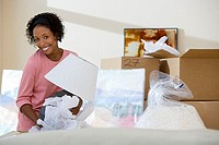 Woman moving house, unpacking lamp from cardboard box in living room, smiling, portrait