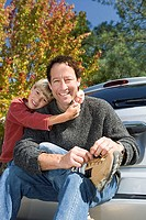 Boy 6-8 embracing father beside car, man sitting on bumper, tying shoelace, smiling, portrait