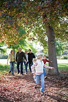 Multi-generational family walking beside tree in park in autumn, two children 6-9 running on ahead