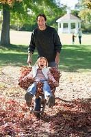 Father pushing daughter 7-9 in wheelbarrow in autumn garden, girl sitting on leaves, smiling, portrait
