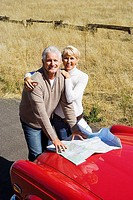 Mature couple standing beside red car on country road, looking at map, smiling, portrait, elevated view