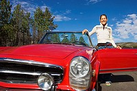 Young woman standing beside red convertible car on country road, smiling, front view, portrait