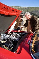 Senior man and adult son experiencing car trouble on country road, looking at engine, side view (thumbnail)