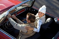 Couple sitting in red convertible car, man driving, woman with arm around man, smiling, portrait, elevated view