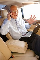 Senior businessman sitting in back-seat of car, using mobile phone and laptop, gesturing with hand, side view
