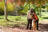 Couple standing with golden retriever in autumn park, arms around each other, smiling, portrait