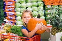 Girl 7-9 standing in vegetable section of supermarket, clutching large pumpkin, smiling, portrait