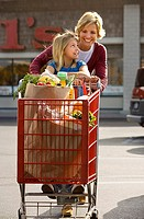 Mother and daughter 7-9 leaving supermarket, woman pushing shopping trolley in car park, smiling, front view