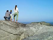 Family standing on rock overlooking Atlantic Ocean, looking at horizon, rear view