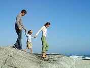 Family walking hand in hand on rocky beach overlooking Atlantic Ocean, side view