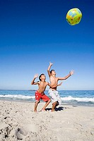 Two boys 6-8 playing with inflatable ball on sandy beach, Atlantic Ocean in background, smiling, side view