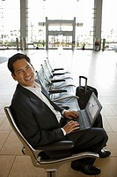 Businessman waiting in airport departure lounge, using laptop, smiling, side view, portrait