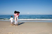 Mother and two children 5-7 standing on sandy beach, looking at Atlantic Ocean horizon, rear view