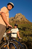 Mature couple standing with bicycles on mountain trail, smiling, low angle view, portrait