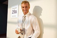 Businessman standing outside meeting room, taking coffee break, casting shadow on wall, smiling, portrait