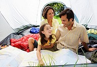 Family sitting inside tent on camping trip, father and daughter 8-10 looking at map, smiling