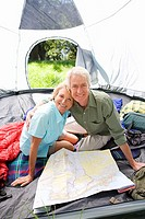 Senior couple sitting inside tent on camping trip, looking at map, smiling, portrait