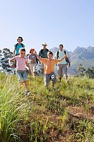 Multi-generational family hiking on mountain trail, boy and girl 8-10 leading, front view