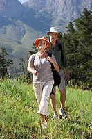 Senior couple, with rucksacks and sun hats, hiking on mountainside, woman leading, front view