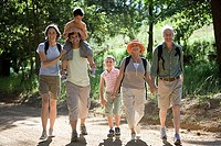 Multi-generational family hiking on woodland trail, boy 8-10 on father's shoulders, smiling, portrait
