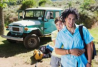 Young couple standing near parked jeep at start of camping holiday, woman embracing man, smiling (thumbnail)
