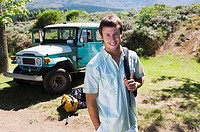 Young man standing near parked jeep at start of camping holiday, carrying rucksack, smiling, portrait