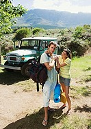 Young couple unloading parked jeep at start of camping holiday, woman assisting man, smiling, portrait
