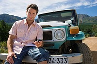 Young man sitting on bumper of parked jeep on dirt track in mountain valley, using mobile phone, portrait