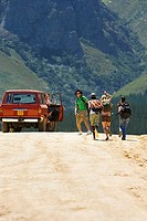 Four young adults, with rucksacks, running up to stationary jeep on dirt track in mountain valley, rear view