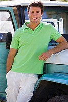 Young man, in green polo shirt, leaning against parked jeep, smiling, portrait (thumbnail)