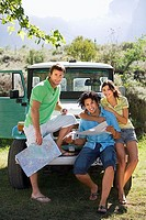 Young woman and two male friends leaning against parked jeep, consulting road map, smiling, portrait