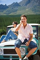 Young couple sitting on bonnet of parked jeep in mountain valley, man using mobile phone, smiling, portrait