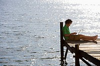 Solitary young man sitting on lake jetty, using laptop, profile