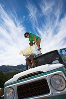 Young couple sitting on roof of parked jeep in mountain valley, consulting road map, smiling tilt