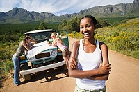 Four young adults consulting map beside jeep on dirt track in mountain valley, focus on woman, smiling, portrait