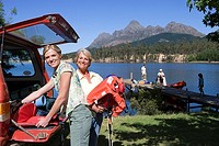 Multi-generational family standing on lake jetty beside boat, senior woman and adult daughter unloading life jackets from SUV