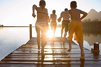 Family, in swimwear, running along jetty, jumping into lake at sunset, rear view lens flare