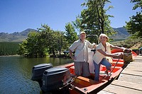 Senior couple standing in motorboat beside lake jetty, woman tying rope to mooring post, smiling, portrait