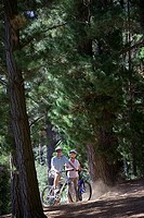 Mature couple, in mid-distance, mountain biking along woodland trail, smiling, side view, portrait