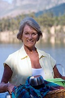 Senior woman carrying picnic hamper beside lake, smiling, portrait